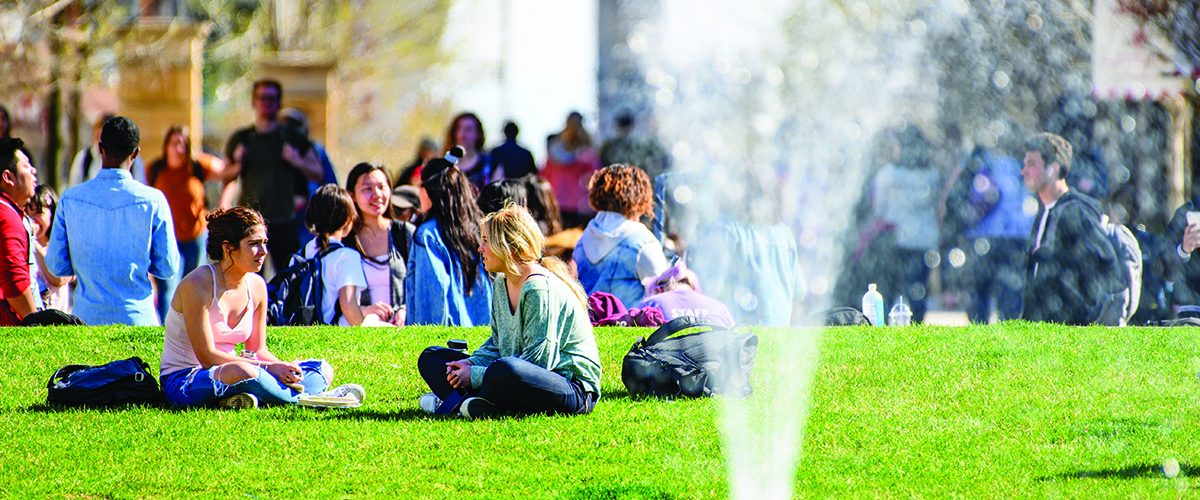 Students in the background sitting on lawn on a warm spring day, the spike of the fountain in the foreground.