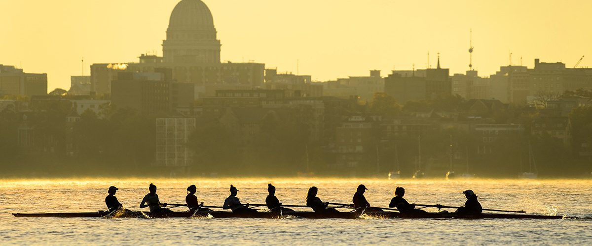 The Wisconsin women's crew team rows along Lake Mendota past a silhouette of the Wisconsin State Capitol Building and downtown Madison skyline