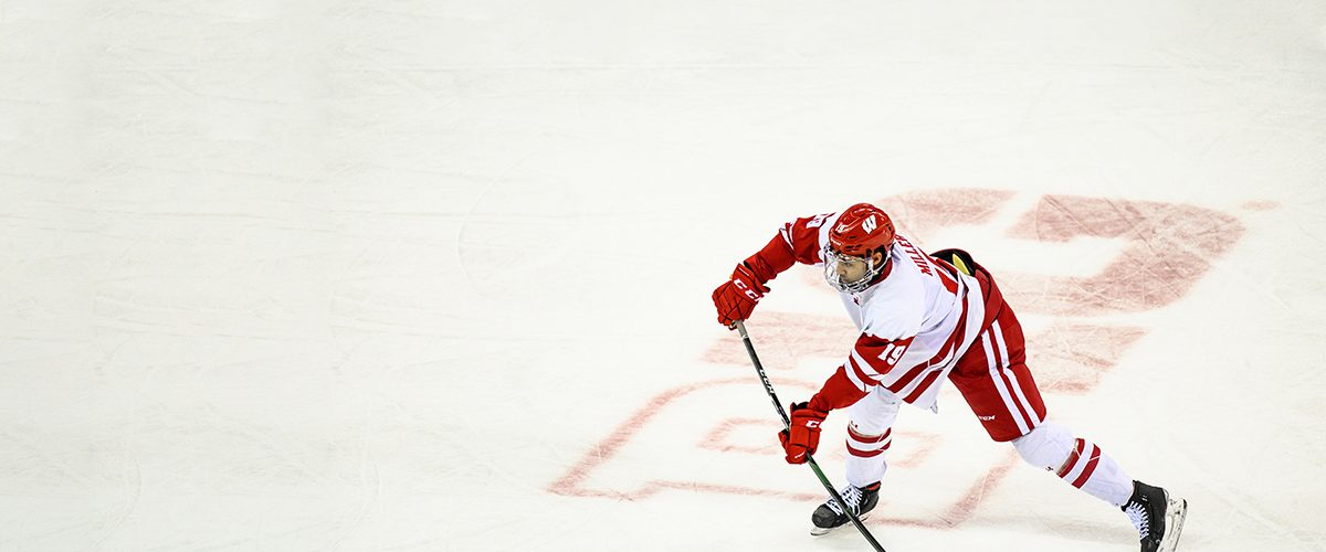 K'Andre Miller advances the puck down the ice during a men's UW Badgers hockey game against Michigan