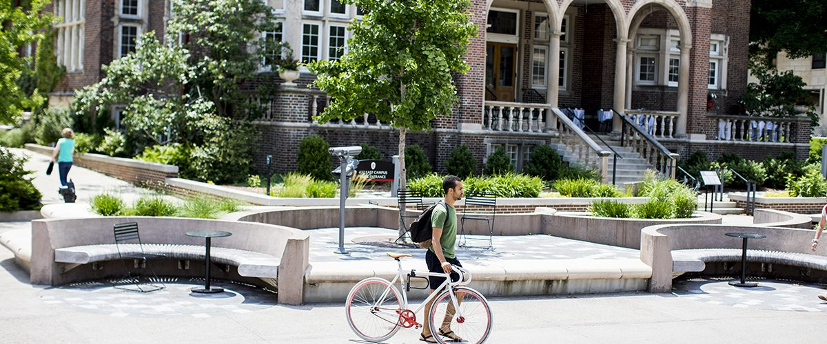 Student walking with his bicycle in front of the University Club building on Library Mall